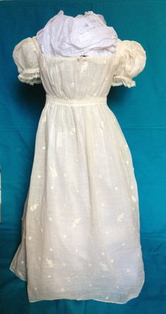 c1820 child's muslin dress. Sprigged embroidery. Ties at back neckline. No fastening at waist. Puff sleeves edged in lace. Evidence of let down tucks in skirt.