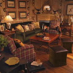 """This family room/den has that definite """"hunt"""" feel with the rich, green velvet sofa, plaid chairs, leather ottomans and antler trophies. A beautiful Federal mirror flanked with pheasants on either side, is a nice focal point for this cozy room. The aviary art work and deer accessories complete the look. I think I see a glass of Blanton's on the rocks in the foreground"""