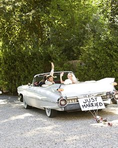 "A vintage car bears the classic ""Just Married"" sign and tin cans."