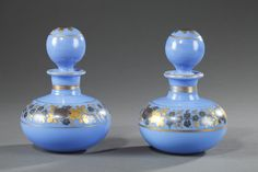 A pair of blue opaline perfume bottles with their ball-shaped cork. Golden stripes suround a gold coloured and dark blue wreath of roses, anemones and forget-me. This delicate decoration is typical of Jean-Baptiste Desvignes, 1820s production.
