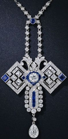 "Art Deco Diamond and Sapphire Butterfly Pendant Necklace, circa 1920s. The ""wings"" are comprised of 6radiant and sizable French-cut diamonds and a pair of square sapphires. The head centers on a bright European-cut diamond framed in electric blue calibre sapphires, and the abdomen features a center row of calibre sapphires framed by diamonds. An old mine pear shape diamond dangles below. 4.50 carats total diamond weight. An applied plaque on the reverse  reads ""K.A.H – A.E.H. 1865-1915""."