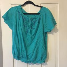 Blue, light fabric Top This shirt is super cute and stylish! It features a loose neckline that can be easily pulled down to sit on your shoulders or at the 'normal' position. It's a vibrant blue with a darker blue embroidery pattern along neckline. Has an elastic waist band and also at the arms. Cute keyhole at top with string bow enclosure. Size L fits (12-14) is 100% cotton Faded Glory Tops Blouses