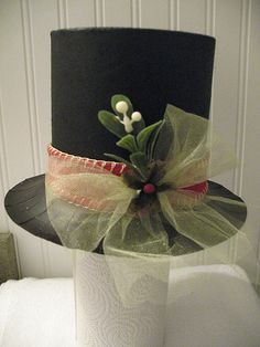 Frosty hat made from 1/2 oatmeal box and paper plate, sprayed black; then embellished.  It is lightweight and does not topple tree.  Unseen on other side is a melting snow drip coming from top of hat made with glue and glitter.  Would make a cute real snowman hat or nice on a table setting.  Use for gift drawing names for next Christmas or for pulling out blessing written by guests, etc. etc.