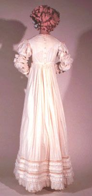 Dress, United States of America, circa 1810. Empire style white cotton gauze dress with long sleeves with tiered shirring and scalloped and embroidered hem. Shown with a stole of Ayrshire embroidery. Kent State University Museum