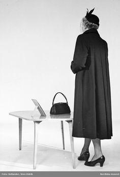 Modell klädd i kappa, hatt med flor och pumps, står framför ett bord med en handväska och en fotoram på. Fotograf: Sten Didrik Bellander, ca 1955-1960