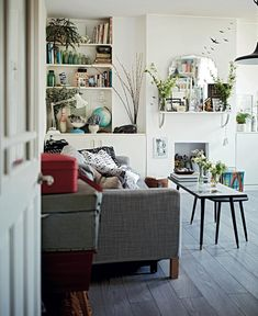 Despite its small size, a huge amount of personality has been packed into the living room. Shelves flank the chimney breast and another was added above the non-working fireplace to provide more surface space for this globe-trotting couple's collections, largely picked up on their travels. Potted plants and vases of branches bring the room to life and last longer than cut flowers.