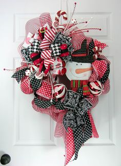 Lots of dots resembling snow in this snowman wreath. A premium red/white deco mesh wreath with loops of red/white dotted ribbon, black/white dotted ribbon, and peppermint accented picks, candy canes a
