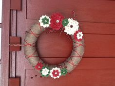 Felt flower wreath- felt flower template available @ makeanddogirl.com/2011/10/tutorial-diy-felt-flowers/  Wrapped a straw wreath in yarn, about one skein of bulky yarn, then used contrasting yarn wrapped in alternating directions to get X pattern. I used buttons for the center of my flowers and attached with a hot glue gun. Add a few accent berries and you have a perfect fall wreath!