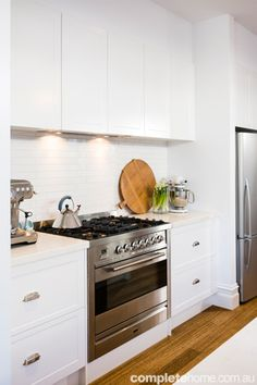 Lovely white kitchen boasts white cabinets paired with white quartz countertops and linear white tiled backsplash framing stainless steel gas stove. Funky Kitchen, Hidden Kitchen, Kitchen Living, New Kitchen, Kitchen Modern, Modern Kitchen Renovation, Kitchen Interior, Kitchen Hoods, Kitchen Cabinets
