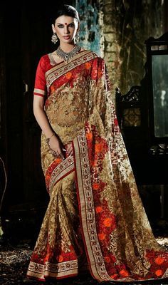 Get in touch with your feminine desire by owning this beige shade net embroidered saree. The appealing aari, jaal, lace, mirror, resham and stones work in the course of the attire is awe-inspiring. Upon request we can make round front/back neck and short 6 inches sleeves regular sari blouse also. #NewAwesomeTrendsetterSaree