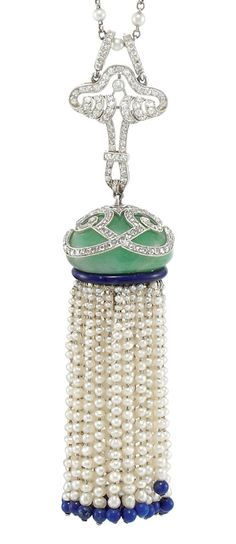 Art Deco Platinum, Diamond, Jade, Blue Enamel, Seed Pearl and Lapis Bead Tassel Pendant with Platinum and Pearl Chain. The delicate chain spaced by seed pearls, joined by a pierced fancy-shaped scrolled diamond-set panel, suspending an oval cabochon jade approximately 17.6 x 21.0 mm., topped by a diamond-set scrolled design, supporting a multi-strand seed pearl fringe tipped by lapis beads, circa 1920.