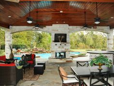 A wood ceiling adds a warm and distinctive look to this stone patio. The palm-tree decoration on the fireplace covers a flat-screen TV. The ambiance of the fireplace can also be appreciated from the vantage point of the spa and pool. Design by HGTV fan Outdoor Rooms, Outdoor Living, Outdoor Decor, Outdoor Kitchens, Outdoor Patio Fans, Outdoor Stuff, Outdoor Projects, Deck Design, House Design