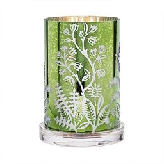 """Our faux mercury glass hurricane brings the shimmering rainforest indoors. Etched with a graceful botanical pattern that lets the silvery interior glimmer through the green exterior. Use with jar and pillar candles, sold separately. Includes silvertone metal three-tealight tree for use with tealights. Candles sold separately. 8½""""h 22 cm h, 6¼""""w 16 cm"""