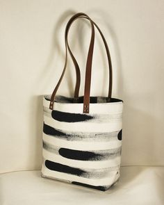 """A super sturdy large natural canvas tote bag with a hand painted stripe in rich black ink. Black or brown leather straps with a 12"""" drop. Interior pocket for easy access to your phone and wallet. Each bag is printed, cut and sewn by hand in SF.16"""" wide, 12.5"""" tall and 4.75"""" deep Diese und weitere Taschen auf www.designertaschen-shops.de entdecken"""