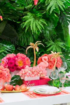 Gold palm tree decoration with a flamingo candle and a gorgeous pink and orange floral arrangements with a green palm leaf wall and pink Kate Spade placemats with Bloom Box Details Details and Cavin Elizabeth Photography