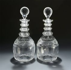 "GEORGE III THREE-RING CUT GLASS DECANTERS England or Ireland, c1800-1810:Of the ""Prussian"" shape, each neck with a wide cut ring to the opening, above a slice-cut neck and shoulders, the necks with three annulated neck rings, all above a band of diamond prism cutting and two bands of finely-cut fluting; retaining the original cut bulls eye stoppers; lightly polished pontils."