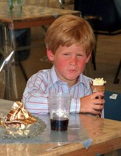 Prince Harry enjoys an ice cream cone, but looks like he isn't happy about having his picture taken.