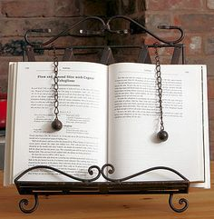 I like the weights on this to hold the pages. http://assets1.notonthehighstreet.com/system/product_images/images/000/124/582/normal_cook_book_stand3.jpg?1286932778