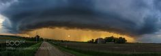 Stormy Sunset A panoramic photo of an approaching thunderstorm during sunset in May of 2014. You'll notice the sun shining through the rain and that provided some great looking colors. This shot was taken with my iPhone 5s I had at the time.