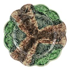 English Leaf Molded Dinner Plate  England  circa 1760  A rare and fine English creamware leaf molded dinner plate decorated in underglaze oxide colors