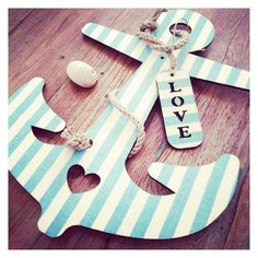 An Anchor Painted Blue And White Stripes That Has A Tag On It That Says Love