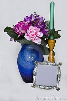 A blank frame and a vase of flowers with a single candle