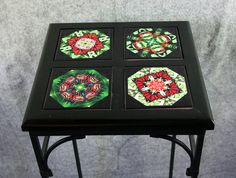 A gorgeous wrought iron side, coffee or end table with ceramic tile top. It has four of my 4x4 inch ceramic tiles installed on a black pine custom crafted wood frame. The wood frame has been installed to the top of this black wrought iron table. The top of this table has a protective acrylic finish and will endure hot items similar to a trivet.