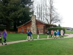 A walking tour returns to the Cabin.  Job Carr Cabin Museum in Old Town Park Tacoma, WA.