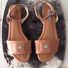 """Longchamp sandals flats camel 40 Longchamp leather flat sandals with ankle strap in rich camel color.  Comes with Longchamp dust bag.  Size 40 euro but fits like a size 9.  I wear a size 8.5 and these are a little big on me.  Made in Italy.  One of the sandals is missing the tag on the footbed (see pic) but only worn a couple of times & are in great shape!  Small 1/2"""" heel but wears like a flat. Longchamp Shoes Sandals"""