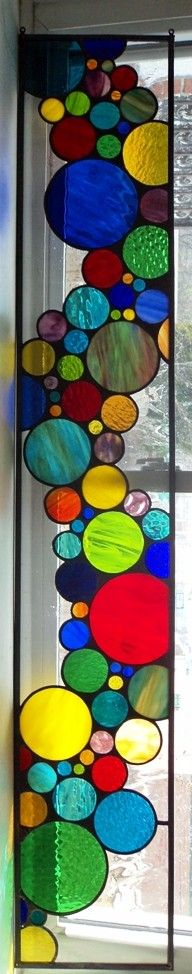 This is a custom designed stained glass window panel that was created to hanging in a long narrow window or sidelight. It measures approximately 9 1/2 inches wide X 57 inches long.  We find these long bubble designs look great when hung or installed horizontally above French doors or vertically in the side light of a front entry door. They add color, interest and privacy to a home.