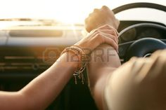 Close up shot of loving couple traveling by car and holding hands Focus on hands of man and woman in Stock Photo