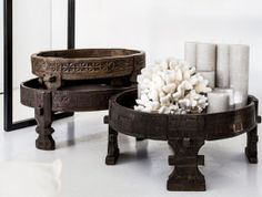 // footstool filled with mismatched pillar candles