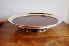 This is a gorgeous, mid century lazy susan by Crescent Silver Co. featuring dark wood grain formica with a silver plated rim and stand. It