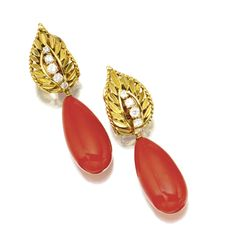 PAIR OF CORAL AND DIAMOND PENDANT-EARCLIPS, VAN CLEEF & ARPELS. Supporting 2 oxblood coral drops, the tops designed as openwork leaves set with 10 round diamonds, mounted in 18 karat gold, signed Van Cleef & Arpels, numbered 65090.