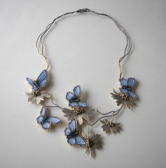 Necklace made of 925 silver and leather. Butterflies in shades of ultramarine textured, painted by hand on skórze.Srebro brushed, washed, in shades of brown and gold. White flowers of chamomile polished, decorated with silver balls oxidized gold. The central portion of the necklace made of a rigid, movable side parts, which makes the necklace is comfortable and nicely arranged on the neck. The length of the necklace is 51 cm.