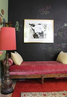 Charcoal chalkboard-painted wall, another wall apple green, raspberry velvet settee, coral lampshade.