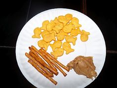 "Dip a pretzel rod in peanut butter and then use that as ""bait"" to pick up/catch the goldfish."