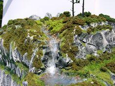 http://www.modeltrainbooks.org/realistic-model-train-water-scenery/ - Amazing waterfall scenery with great looking rock ridge