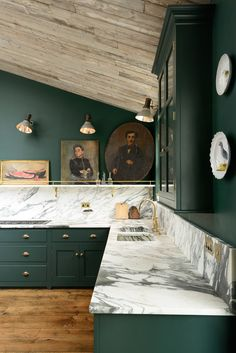 Love the dramatic and very English combination of forest green cabinetry, brass hardware and Calacatta marble counters and backsplash.