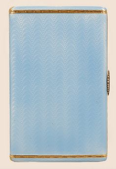 A Faberge silver gilt and guilloche enamel cigarette case, workmaster August Hollming, St Petersburg, 1908-1917. The rectangular case covered in translucent pale blue enamel over an engine-turned wave pattern ground with chased gilt bands and diamond-set thumbpiece.