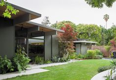 In the back, ferns and other shade-friendly plants thrive beneath the home's deep overhangs.