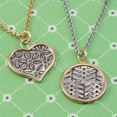 "Hand stamped pendants.  These necklaces are especially beautiful and unique because the patterning resembles beautiful printed fabrics like those of current designers,  Orla Kiely and Marimekko.  Try a hand at this cool techniqe yourself with the book ""New Directions in Punched Metal Jewelry"", and then pop your masterpieces into some of our perfect, lovely frames!"