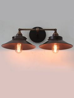 039604 Double wall light with shades finished in pewter and the conjoined arm finished in antique brass. Finished with two exposed filament lamps. Size: Width - 430mm Height - 170mm Diameter of s