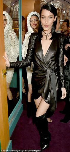 Hell for leather: Showcasing her personal style, Bella Hadid sported a sultry plunging leather mini dress that featured a kimono style belt while Kendall displayed her gold tooth