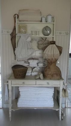Like the brown tones/neutrals mixed with the white.  Nice way to display table clothes/linens.