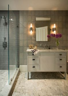 The flooring is hexagonal Carrara marble tiles. The shower has contemporary gray glass tiles. The wall covering has a shagreen look.