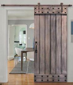 porte de grange coulissante en bois naturel avec des éléments en fer, tapis à rayures