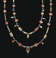 A ROMANO-EGYPTIAN GOLD AND GLASS BEAD NECKLACE CIRCA 200 B.C.-200 A.D. Composed of mosaic glass beads, some disk-shaped, with facing heads on a red ground, some tabular, with a bird on a red or yellow ground, interspersed with four gold Bes-head pendants, a gold amphora pendant with zoomorphic handles, and a drop-shaped pendant interspersed with multicolored glass, faience and gold spacers; strung in two strands with a hook-and-loop closure