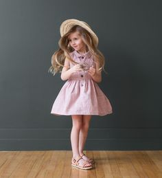 RESTOCKING EARLY APRIL This sleeveless dress features a peter-pan collar, buttons up the front, and a rosie pink color fabric with a white check detail. Fits pr
