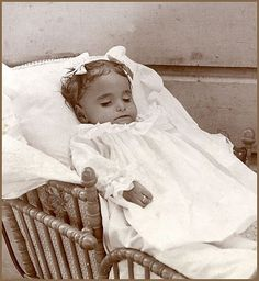 Baby girl in a wicker carriage with a ring on her finger